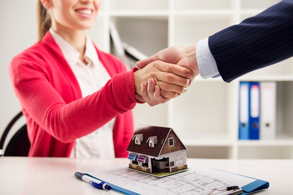 Property Managers Shaking Hands over a Model House