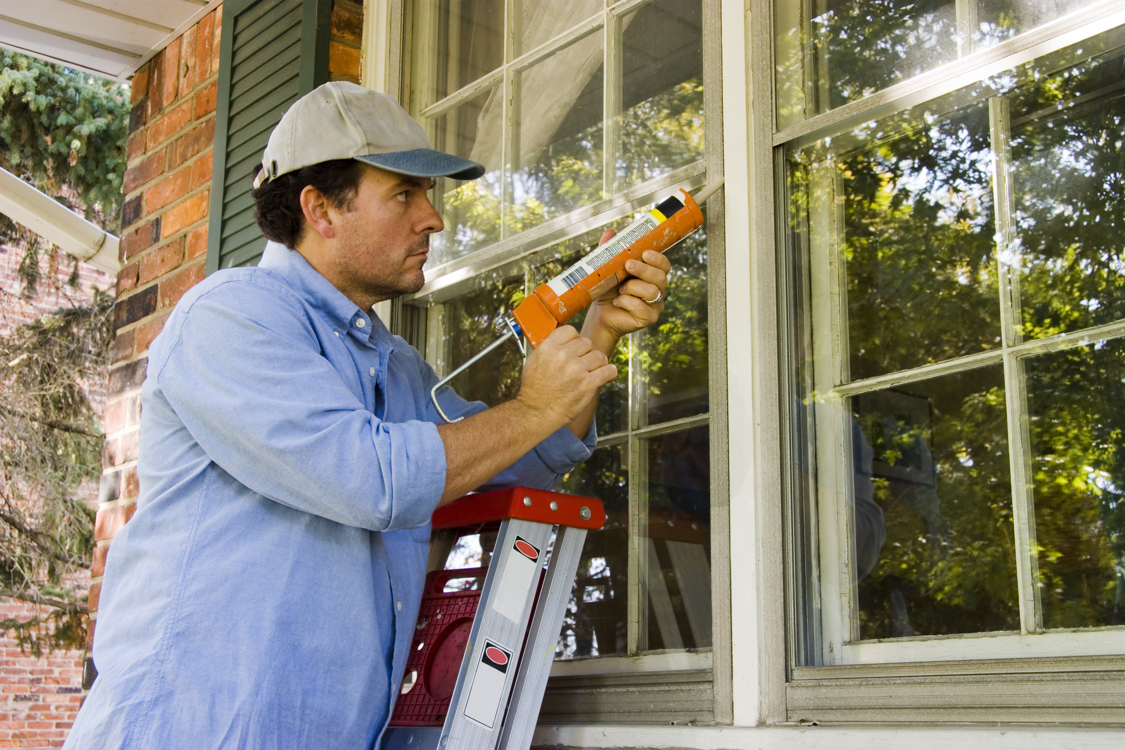 Man Caulking & Weather Stripping WIndow for Rental Property